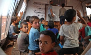 Syrian children originally from Hama attend a class at a makeshift school for displaced people in rebel-held Atme in Syria's Idlib province