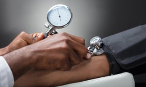 Close-up Of Male Doctor Measuring The Blood Pressure Of Patient Against Gray Background