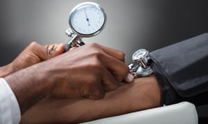 Close-up of a doctor measuring a patient's blood pressure.