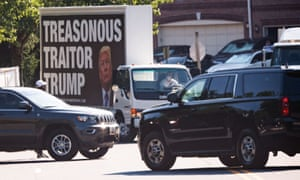 A truck displays a sign of protest as the presidential motorcade arrives on Saturday at Trump National Golf Club in Sterling, Virginia.