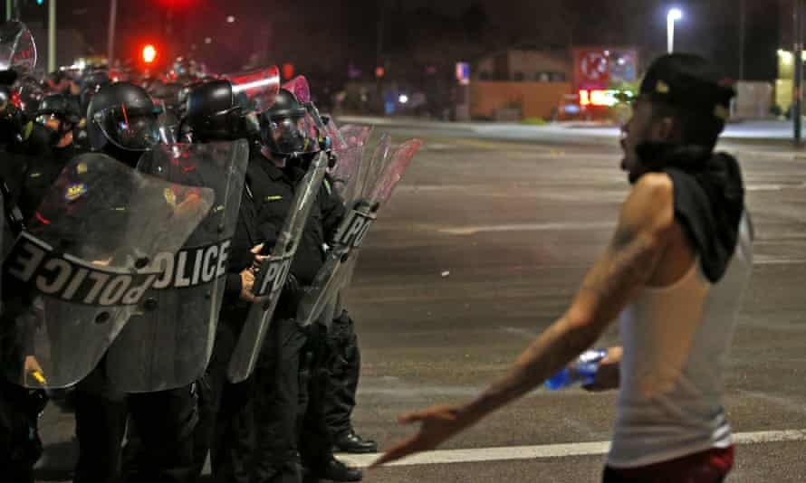 A protester questions police dressed in riot gear as marchers numbering nearly 1,000 take to the streets to protest on Friday in Phoenix.