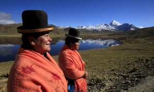 Aymara indigenous women Lidia Huayllas, 48, and Dora Magueno, 50, stand near Milluni lake, with Huayna Potosí mountain in the background