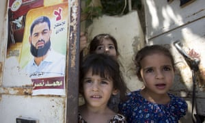 Girls by poster of their uncle Mohammed Allan