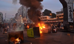 Lebanese anti-government protesters burn dumpsters to block al-Nour Square in Lebanon's northern port city of Tripoli on Tuesday.