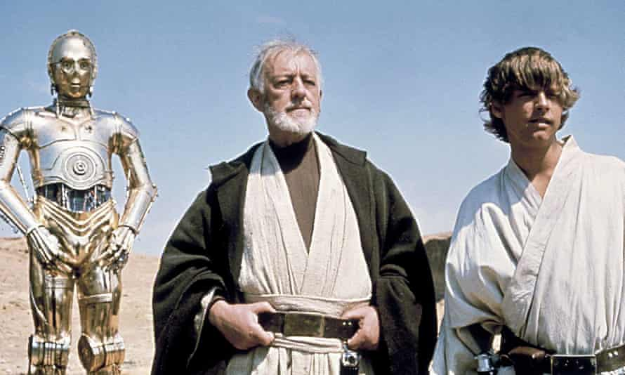 C3-P0 (Anthony Daniels), Obi-Wan Kenobi (Alec Guinness) and Luke Skywalker (Mark Hamill) stand against a blue sky, looking into the distance in a desert.