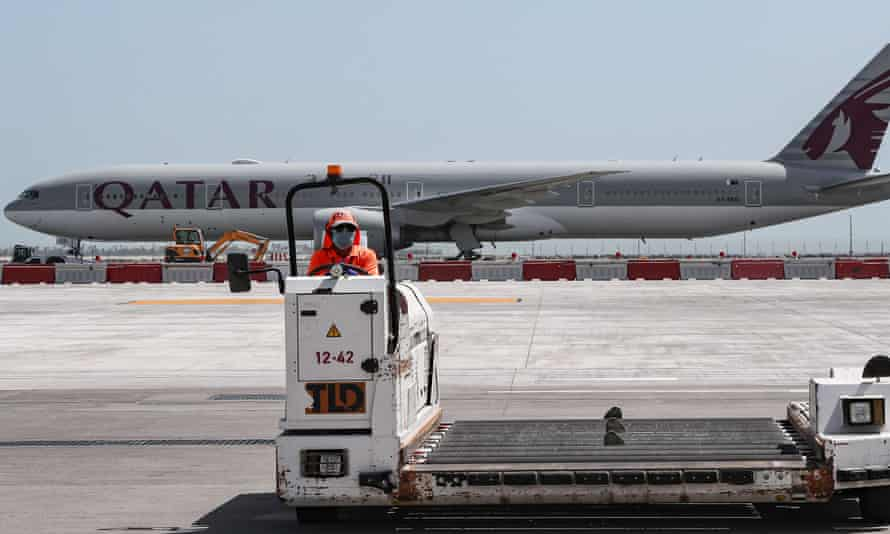 An airport worker wearing a face mask drives a luggage trolley at Doha airport