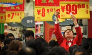 A worker puts up a promotion in a Chinese supermarket.