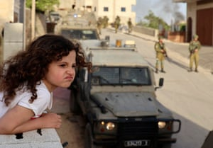 Aqraba, West BankA Palestinian girl watches from the balcony of her house as Israeli soldiers conduct a security operation in the village east of Nablus.