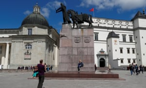 People take a picture next to a monument in Vilnius, Lithuania