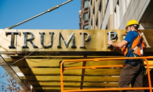 A worker takes down lettering reading 'Trump Place' from the facade of an apartment complex in New York on 16 November 2016.