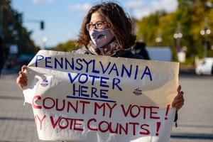 Berlin, Germany. A Joe Biden supporter holds a sign that reads: 'Pennsylvania Voter here. Count my vote! My vote counts!' next to the Brandenburg Gate