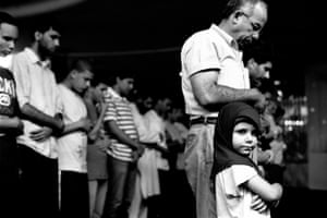 A young girl at prayers with her father at the Muslim American Society in Brooklyn, New York
