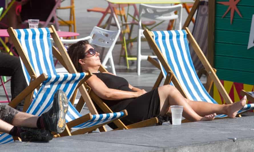 A woman sunbathes on a deckchair in London