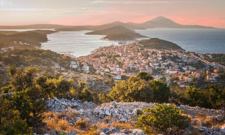 A view across houses built into the hillside, the sea and a sunset on Losinj island