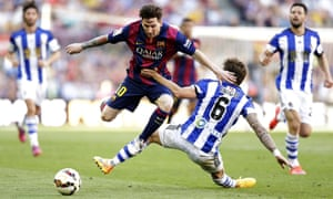 FC Barcelona's Lionel Messi, left, duels for the ball against Real Sociedad's Inigo Martinez
