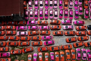 Dozens of pink and red cars from above