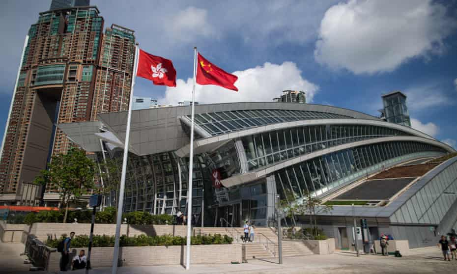 The Hong Kong and China flags outside the West Kowloon station in Hong Kong.