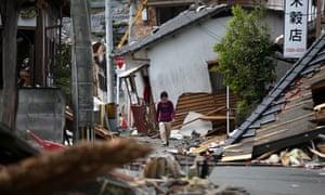 A man walks past collapsed houses on 20 April in Mashiki near Kumamoto, Japan