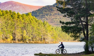 A teenager cycles to the edge of Loch an Eilein.
