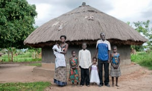 Eunice and Bosco with their family in front of their hut in Gulu, Uganda.