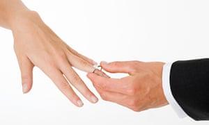 Groom placing ring on brides finger