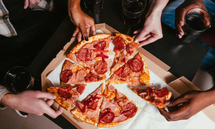 People sharing pizza with salami and ham