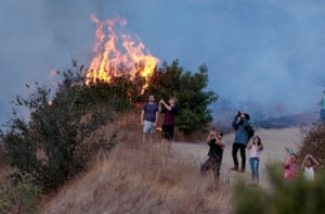 Spectators watch a helicopter fly over the La Tuna Canyon fire over Burbank, California