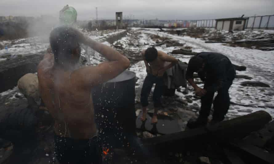 People wash themselves outside a makeshift shelter