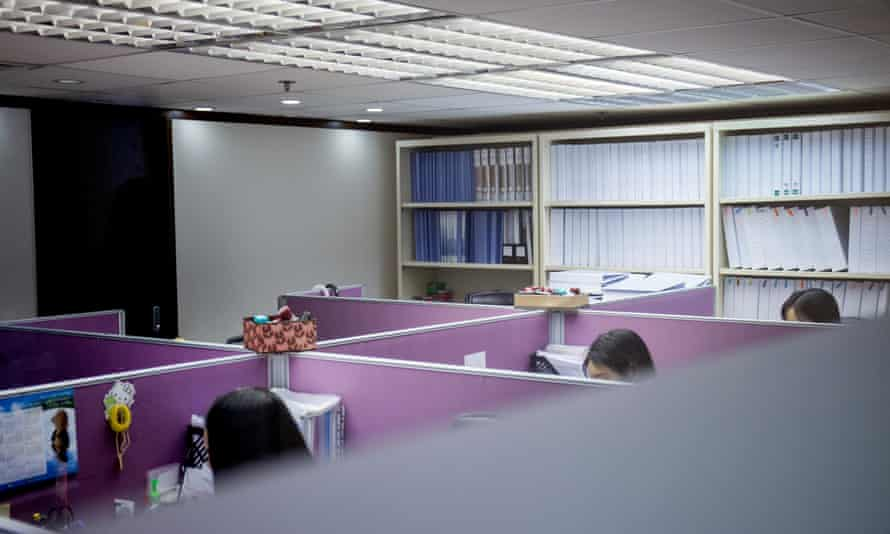 PRG staff work while potential clients meet in the firm's office in Wan Chai.