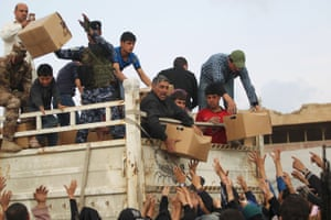 Displaced Iraqis from Mosul receive aid parcels as they arrive at the Hamam al-Alil camp earlier this month