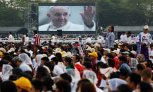 Catholic faithful watch a video of Pope Francis during a mass at Kyite Ka San football stadium in Yangon.