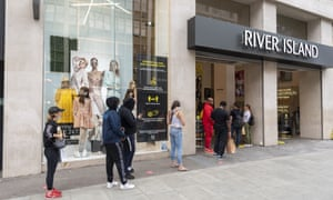 People queue outside the River Island store on London's Oxford Street after the shops were allowed to reopen.