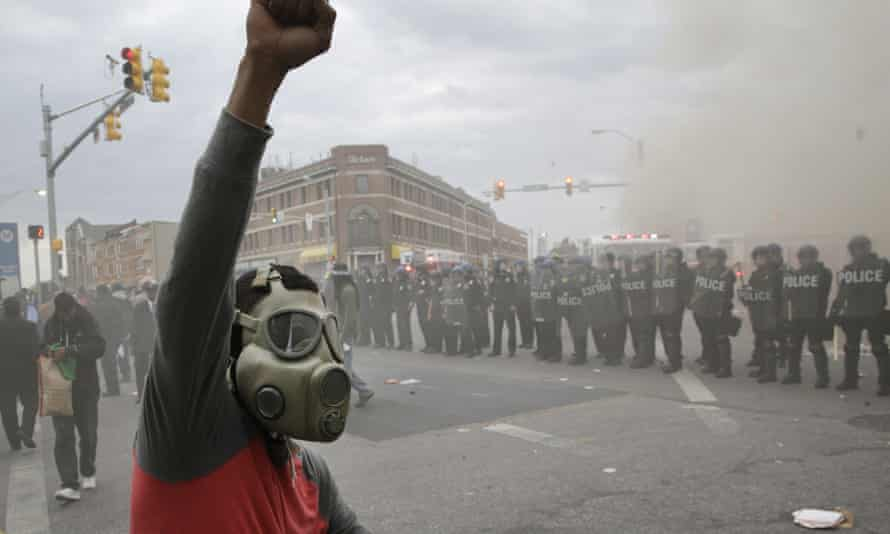 A demonstrator raises his fist as police stand in formation on 27 April 2015, during unrest following the funeral of Freddie Gray in Baltimore.