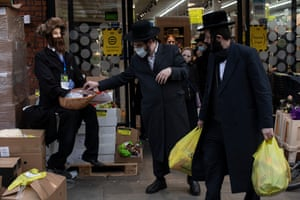 Men take masks at a supermarket in London. This year Purim is to be scaled back significantly, with Rabbis asking that, among other measures, mishloach manot – traditional gifts of food to family and friends – be left on doorsteps with people stepping back to a safe distance