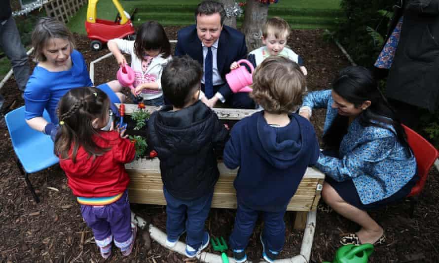 David Cameron plants flowers alongside children at a nursery in London