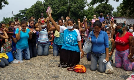 Relatives of inmates pray outside Los Llanos penitentiary after a riot left dozens of dead amid the coronavirus outbreak in Guanare, Venezuela, on 2 May.
