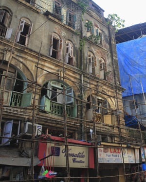 Decaying buildings line the streets, precariously supported by bamboo poles