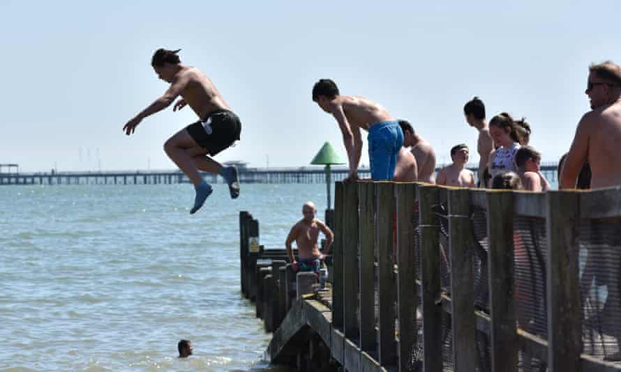 People jump from a jetty into the sea in Southend
