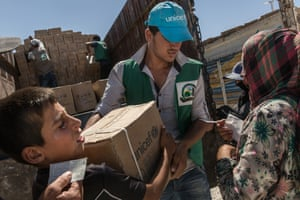 Refugees exchange vouchers they get upon arrival for supplies distributed by a Unicef relief worker at the Ain Issa camp
