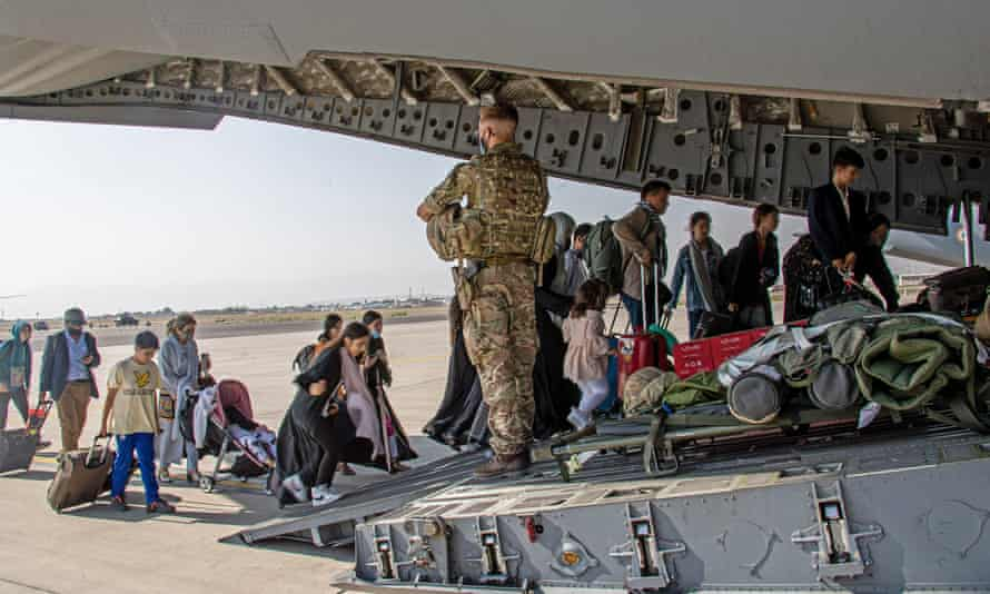 Afghan evacuees board military transport plane