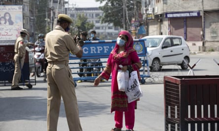 A Kashmiri woman asks a police officer if she can cross the road in Srinagar.