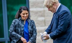 Boris Johnson and Priti Patel sanitise their hands.