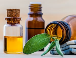 Bottle of essential oil with  fresh sage leaves on old wooden background.