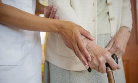 Close-up of caretaker helping older woman walk