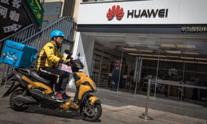 A delivery man rides on a scooter past a Huawei store in Beijing