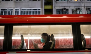 A passenger wearing a protective mask uses her phone on bus in Hong Kong