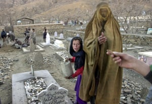 Kabul, 2002. A burqa-clad woman accepts money from a passerby as she stands next to the grave of a relative at the Tamim Ansar cemetery in the outskirts of Kabul.