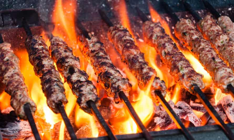 Spicy Seekh kebabs on skewers on a barbecue grill in London
