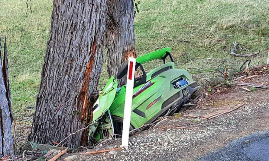 A green Porsche lies smashed into two gum trees