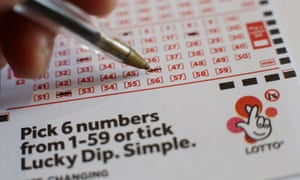 Someone choosing numbers with a biro on a lottery draw sheet